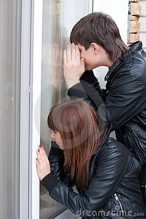 Young couple peeping in window