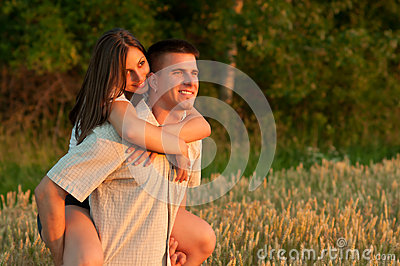 Young couple piggyback riding and watching sunset