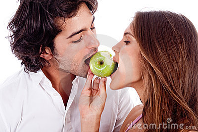 Young couple playfully biting green apple