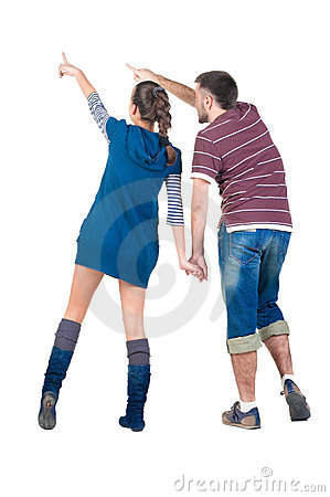 Young couple pointing at white wall .