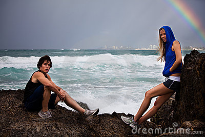 Young Couple Posing on Rocks By Stormy Ocean