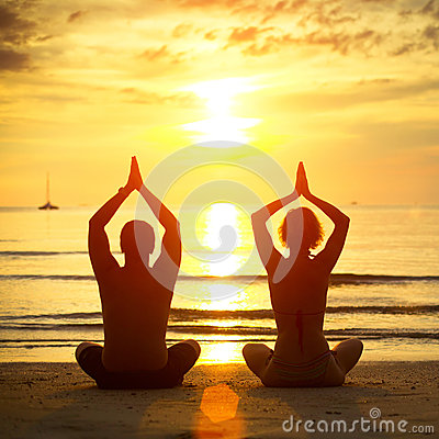 Young couple practicing yoga on the beach