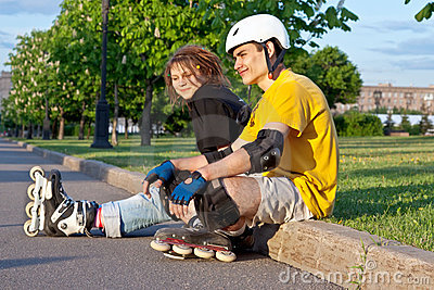 Young couple put on inline skates