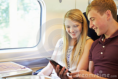 Young Couple Reading A Book On Train Journey