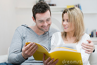 Young couple reading magazine