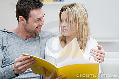 Young couple reading magazine with love