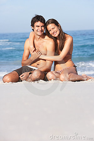 Young Couple Relaxing On Beach Wearing Swimwear