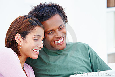 Young couple relaxing in front of a laptop