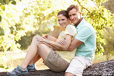 Young Couple Resting On Tree In Park