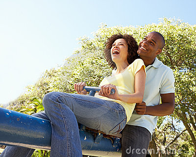 Young Couple Riding On SeeSaw In Park