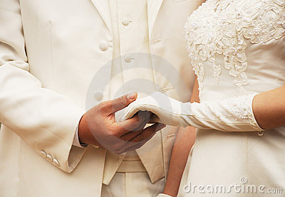 Young couple in robe holding hands