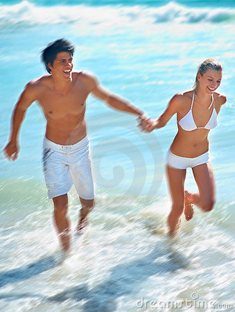Young couple running at the beach