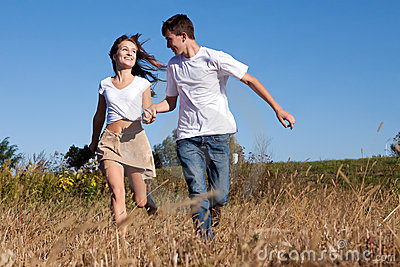 Young couple running on summer meadow