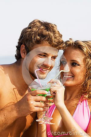 Young couple on the seaside with cocktails