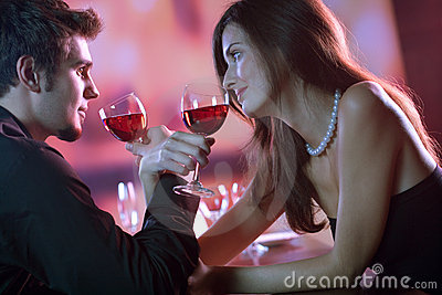 Young couple sharing a glass of red wine in restaurant, celebrat