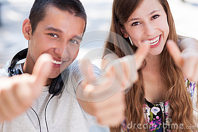 Young couple showing thumbs up