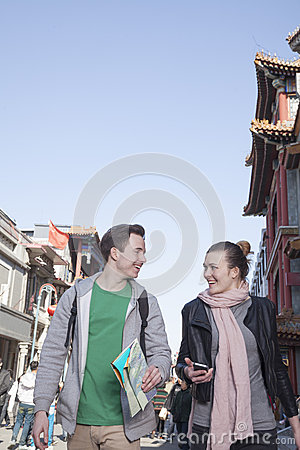 Young couple sightseeing, holding map and mobile phone.