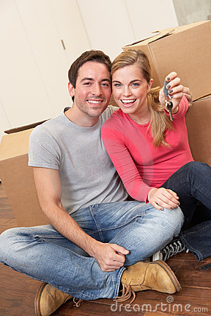 Young couple sit on the floor holding key in hand