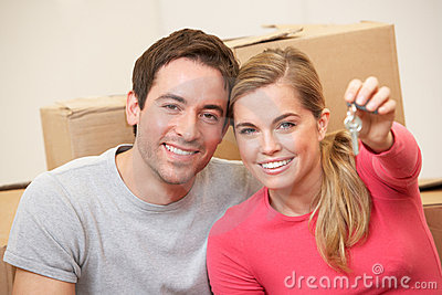 Young Couple Sit On The Floor Holding Key In Hand Royalty Free Stock Photos - Image: 18044538