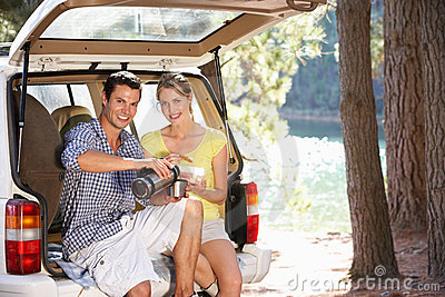 Young couple sitting in back of car boot