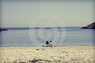 Young couple sitting on the beach and looking at sea