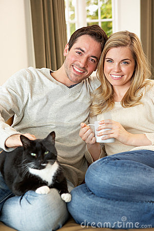 Young couple sitting with cat on sofa