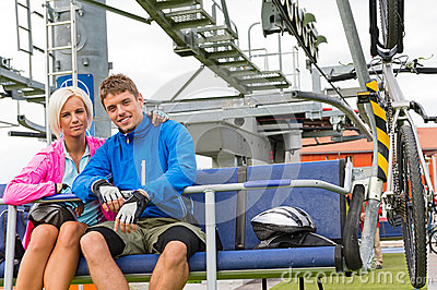 Young couple sitting chair lift waiting departing