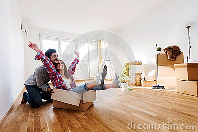 Young couple sitting on the floor of empty apartment. Move in to new home. Stock Photo