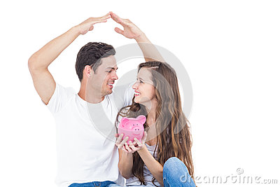 Young couple sitting on floor with piggy bank Stock Photo