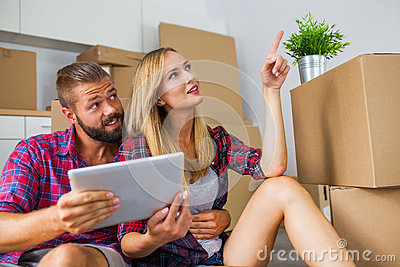 Young couple sitting on the floor with tablet pc and choosing fu Stock Photo