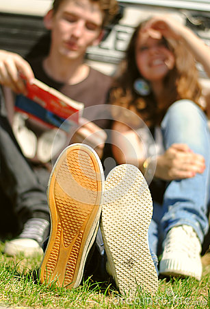 Young couple sitting near auto closeup feet image