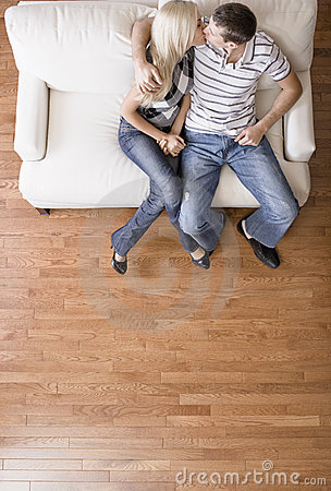 Free Young Couple Sitting On Love Seat Kissing Stock Photography - 12731482