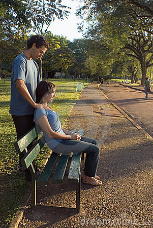 Young Couple sitting on a Park Bench - Vertical