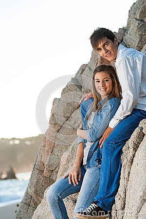 Young couple sitting on rocks at seaside.