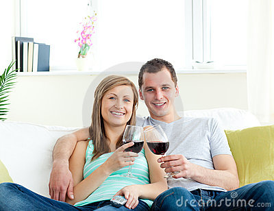 Young couple sitting on the sofa drinking wine
