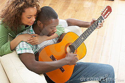 Young Couple Sitting On Sofa Playing Guitar