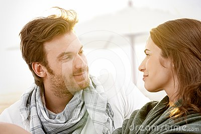 Young couple sitting on summer beach smiling