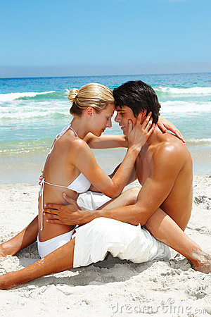 Young couple sitting together at the beach