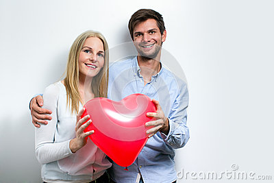 Young couple smiling and holding a heart