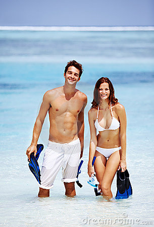Young couple with snorkelling gear at the beach