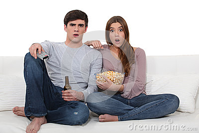 Young couple on sofa with popcorn and beer
