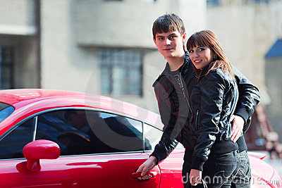 Young fashion couple in love at the sport car