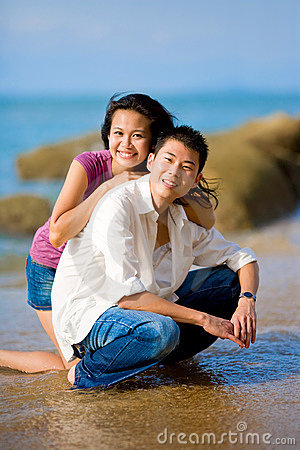 Young couple squating by the beach happily