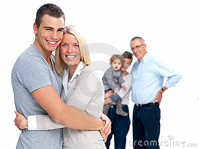 Young couple standing with family in the backgroun
