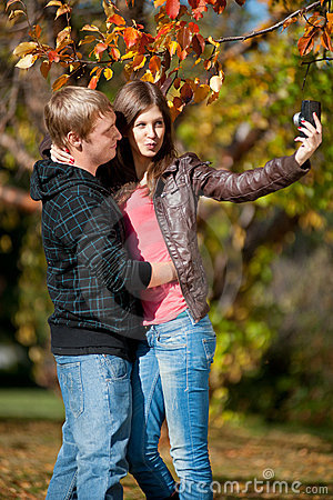 Young couple taking pictures of themselves in park