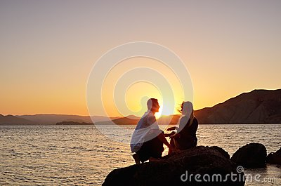 Young couple talking on a rock by the sea