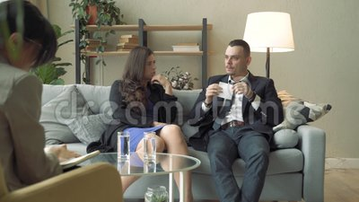 Young couple talking to a specialist or consultant in a modern office.  stock footage