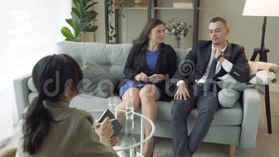 Young couple talking to a specialist or consultant in a modern office.  stock video