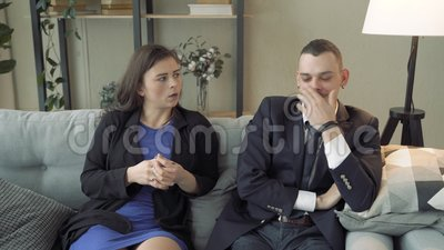 Young couple talking to a woman specialist or consultant sitting on a sofa in a modern office.  stock footage
