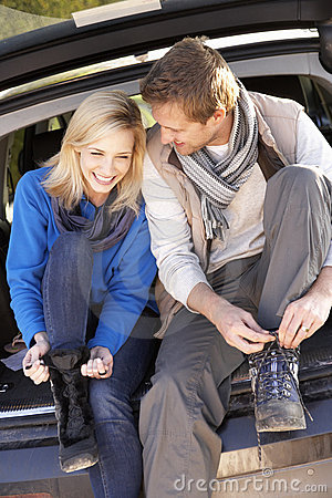 Free Young Couple Tie Boots At Rear Of Car Stock Photo - 17490650